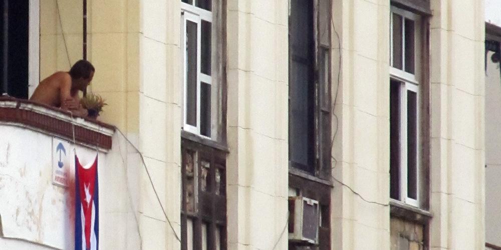 Hombre mirando hacia la calle desde un balcón de la Habanaa, Cuba. Historias de la Habana.